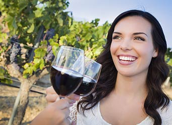 Woman Smiling with Wine at a Winery