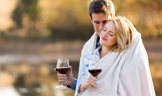 A Man and Woman Drinking Wine Covered in a Blanket